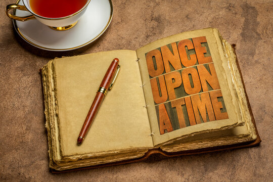 once upon a time opening phrase - storytelling concept - wood type word abstract in a retro journal with a cup of tea