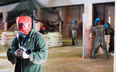 Fototapeta Portrait of red team cheerful player who is aiming in opponents on paintball field.