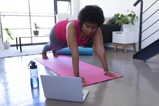 African american woman using laptop exercising wearing sports clothes