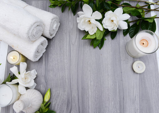 Spa composition with white gardenia andcandle , and herbal ball , on wooden texture background