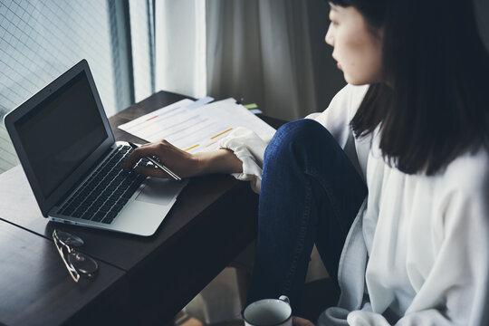 パソコンを見ながらくつろぐ女性