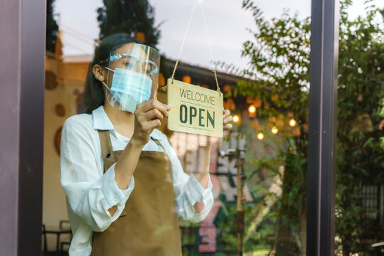 Asian business owner Asian business owner woman wear protective face mask and face shield hanging open sign at her restaurant / cafe, open again after lockdown for new normal
