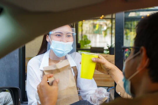 Asian man in protective mask taking food bag and coffee with woman waitress wearing face mask and face shield at drive thru during coronavirus outbreak..