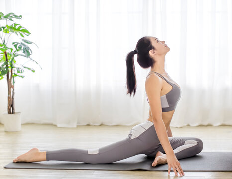 young woman in sportswear doing fitness stretching exercises at home