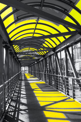 Aboveground pedestrian crosswalk in the trending colors of 2021 illuminating and ultimate gray. A long bridge made of iron and glass, illuminated by the sun. Modern architecture of the city.