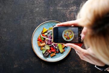 Fototapeta Porn food. Tofu smażone z warzywami.  Kuchnia orientalna. Propozycja podania potrawy. Kobieta robi zdjęcie potrawy komórką. obraz