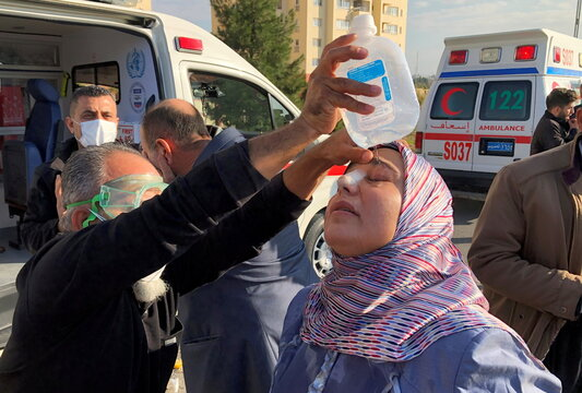 A paramedic tends to a woman who was affected by tear gas during a protest over unpaid salaries of the public servants by the Iraqi Kurdish regional government, in Sulaimaniyah