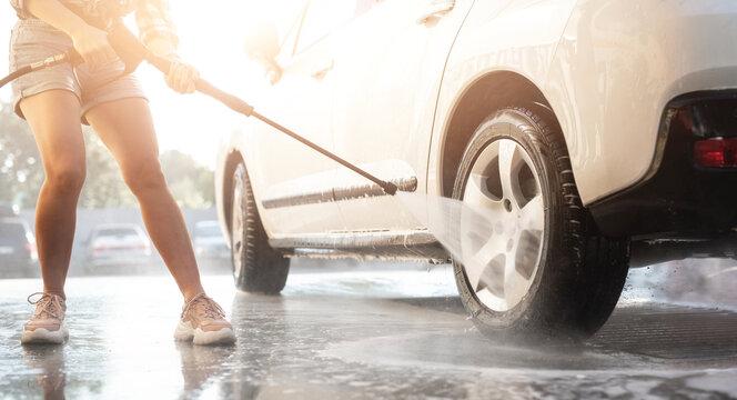 Girl using pressure water on self service car wash