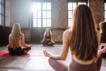 Four young women do complex of stretching yoga asanas in loft style class. Females meditate in lotus position with closed eyes.