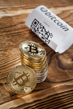 Bitcoin golden coins and paper receipt isolated on a black wood background