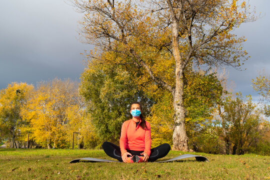 Sporty dressed woman doing stretching in the lotus flower position on a mat in the park wearing a mask to protect herself from the coronavirus