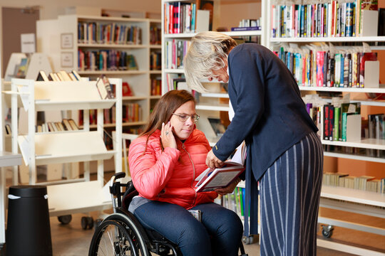 Woman on wheelchair talking to librarian