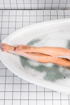 Top view of legs of woman in bathtub with lather