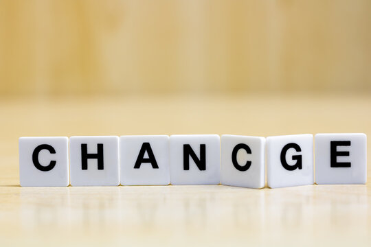 A row of small white plastic tiles, containing the letters forming the word chance or change, to represent the concept of seize the opportunity that change offers.