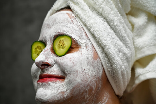 A woman applies a face mask and uses cucumber slices to solve skin problems around the eyes. An ecological, vegan, vegetarian way of life. Self-care and lifestyle, solving skin issues.