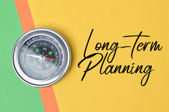 Top view of compass over colorful paper written with text LONG-TERM PLANNING. Business and education concept.