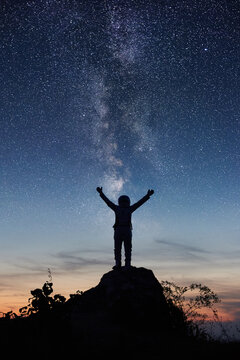 Vertical shot of space traveler standing on rocky hill with night beautiful sky and Milky way on background. Silhouette of cosmonaut in space suit looking at stars and spreading arms out to sides.