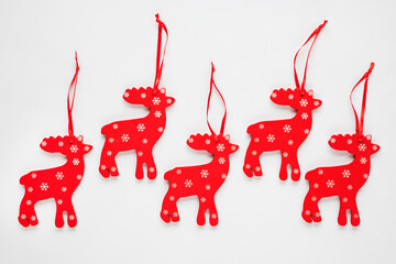 Wooden Christmas decorations. Red deer with white snowflakes on a white background. Christmas and New Year concept.
