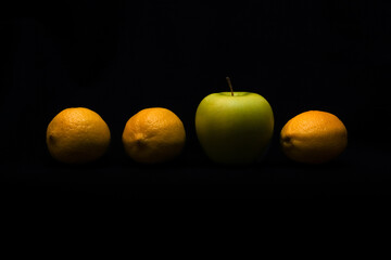 Fototapeta Stand out and be different concept. Apple among lemons on dark background obraz