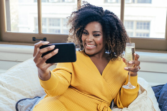 Portrait of a  happy smiling  woman celebrating with Champagne glass on a phone video call at home on couch