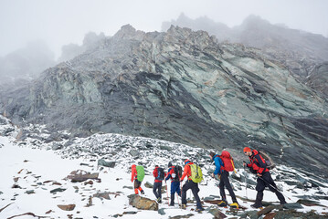 Group of male alpinists with backpacks and trekking sticks having winter hiking tour in mountains, walking on rocky path covered with snow. Concept of travelling, hiking and mountaineering.