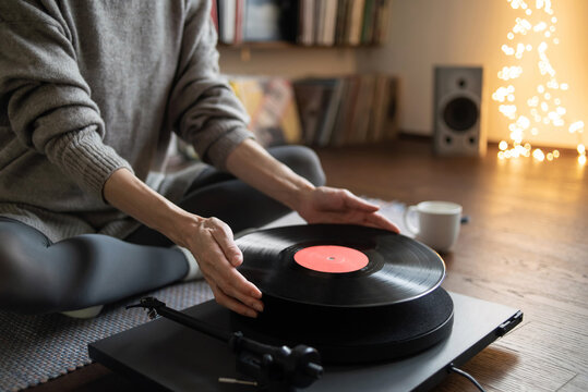 Young woman listening to music, relaxing, enjoying life at home. Girl wearing warm winter clothes having fun. Turntable playing vinyl LP record. Leisure, music, hobby, lockdown, lifestyle concept