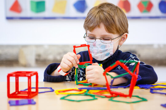 Little child with medical mask playing with lots of colorful plastic blocks kit in preschool nursery or elementary school. Cute child use protective equipment as fight against covid 19 corona virus.