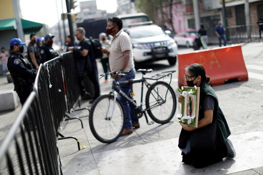 A faithful prays at the Basilica of Guadalupe entrance that is temporarily closed to avoid crowds on the traditional day of celebration of the Virgin of Guadalupe