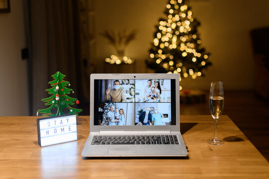 A laptop on the table with a several families on the screen in cozy living room decorated to Christmas. Virtual meeting, video call, online celebration with a family on the distance due to pandemic