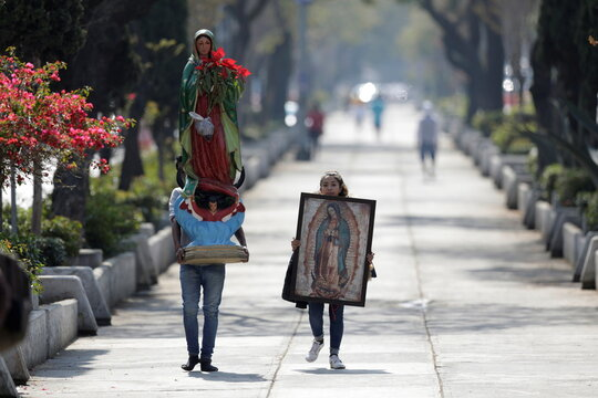 Faithful walk in the vicinity of the Basilica of Guadalupe entrance that is temporarily closed to avoid crowds on the traditional day of celebration of the Virgin of Guadalupe