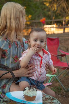 Little girl holds one year old baby boy eating a cupcake.