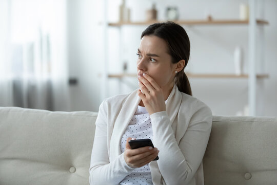Close up upset unhappy young woman holding smartphone, thinking about problems, stressed frustrated girl received bad news in email or message, waiting for boyfriend call, sitting on couch alone