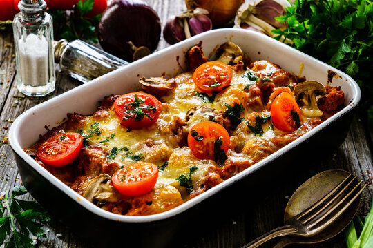Noodle casserole with minced meat, mozzarella cheese and vegetables on wooden table