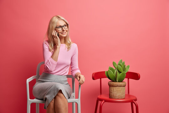 Pleased blonde middle aged woman has telephone talk sits on comfortable chiar spends free time at home looks aside wears spectacles jumper and skirt isolated over pink background. Communication