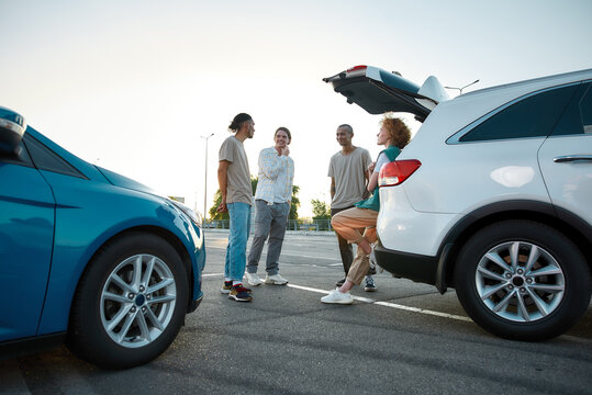 A group of four young casually dressed people speaking to each other smiling and standing together outside on a parking site with cars around