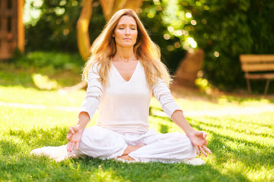 Beautiful mature woman meditating in green sunny garden, healthy lifestyle