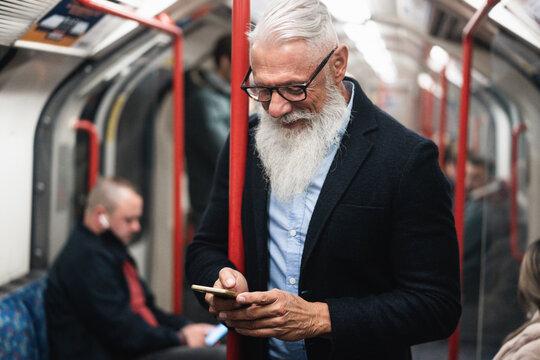 Happy hipster senior man using smartphone in subway train underground - Focus on face