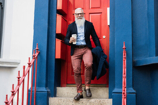 Hipster senior man drinking coffee while walking out from home - Focus on face