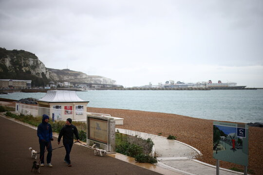 People walk by a beach with the Port of Dover in the background