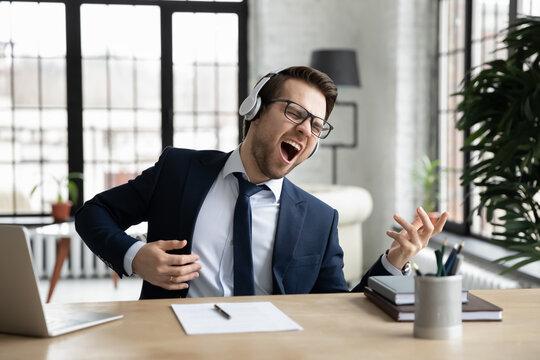 Funny overjoyed businessman wearing headphones pretending playing guitar, sitting at desk in modern office, excited employee executive singing, listening to favorite music, having fun during break
