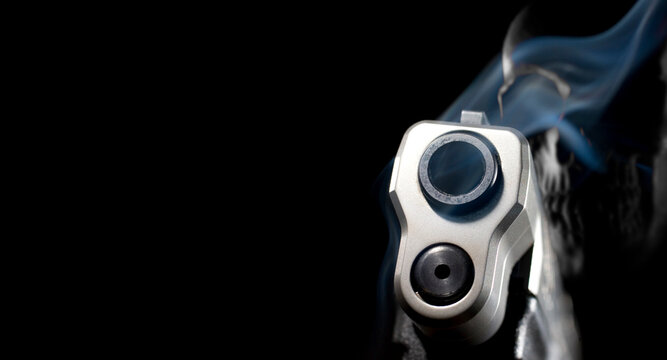 3D illustration of a ghost gun with smoke coming from a pistol barrel and skull behind