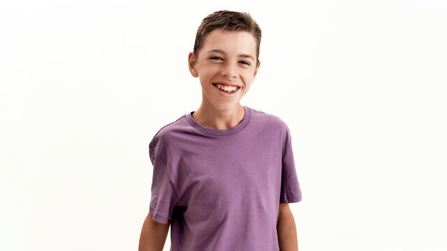 Portrait of happy teenaged disabled boy with cerebral palsy laughing at camera while posing, standing isolated over white background