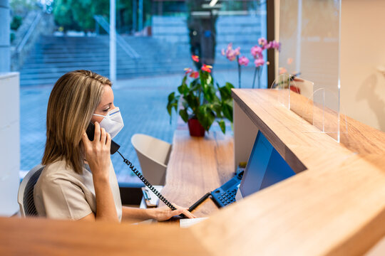 young woman answer the phone at the reception with coronavirus mask