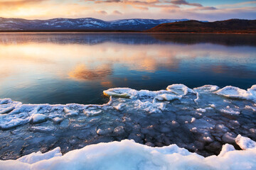 Ice on the frozen lake at sunset. Mountains and sky are reflected in the ice surface of the lake. Beautiful winter landscape. South Ural, Russia