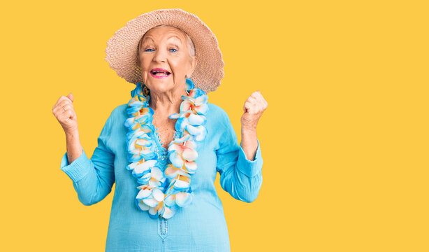 Senior beautiful woman with blue eyes and grey hair wearing summer hat and hawaiian lei screaming proud, celebrating victory and success very excited with raised arms