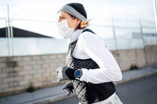 Sportsman with mask running through the industrial zone in winter as the sun rises.