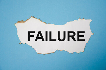 Fototapeta the word failure is written on a white sheet of paper that lies on a blue sticker