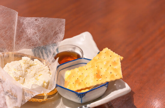 Japanese dessert dish of homemade basket-filled fresh cream cheese made from Hokkaido island cheese in north of Japan with sweet honey sauce and saltine crackers lightly sprinkled with coarse salt.