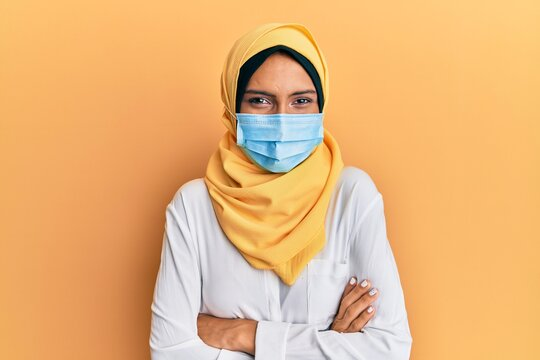Young brunette arab woman wearing traditional islamic hijab and medical mask happy face smiling with crossed arms looking at the camera. positive person.