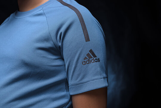 the sleeve and the front of the sports blue t-shirt with the logo of the german company adidas on an isolated background